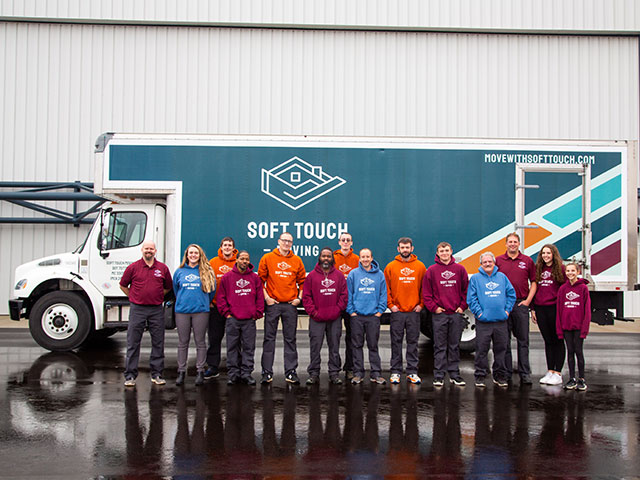 Soft Touch Moving personnel proudly in front of a Soft Touch Moving truck