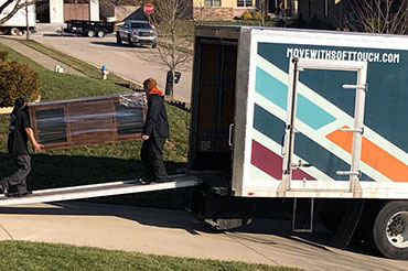 Two Soft Touch Moving professionals loading a Soft Touch Moving truck